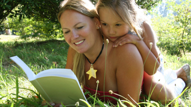 woman-and-girl-reading-book-in-the-park